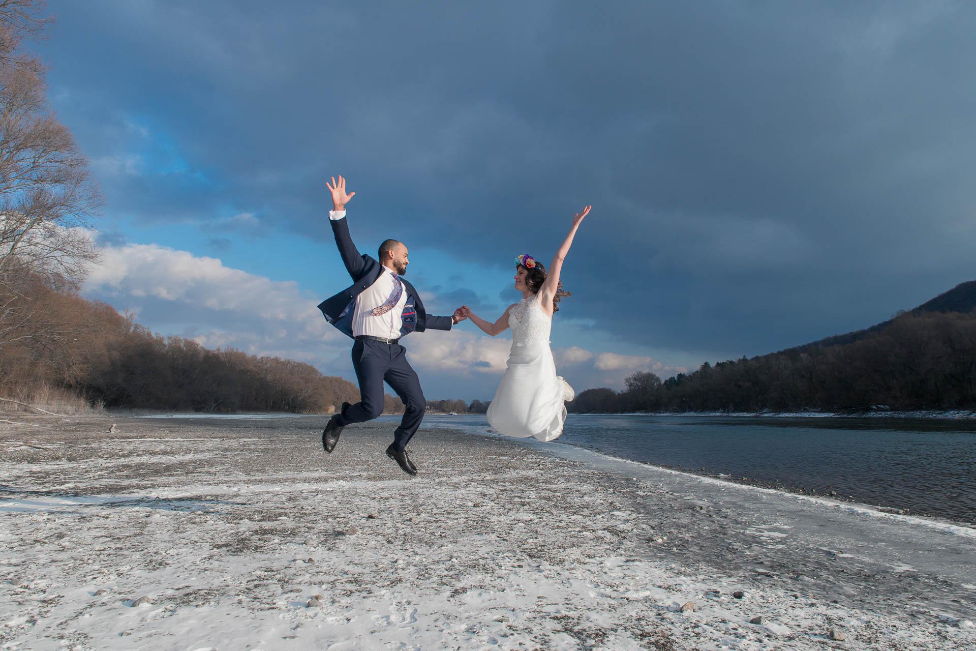Adventure wedding in Hungary - hiking and kayaking - wedding couple jumping in joy at riverside