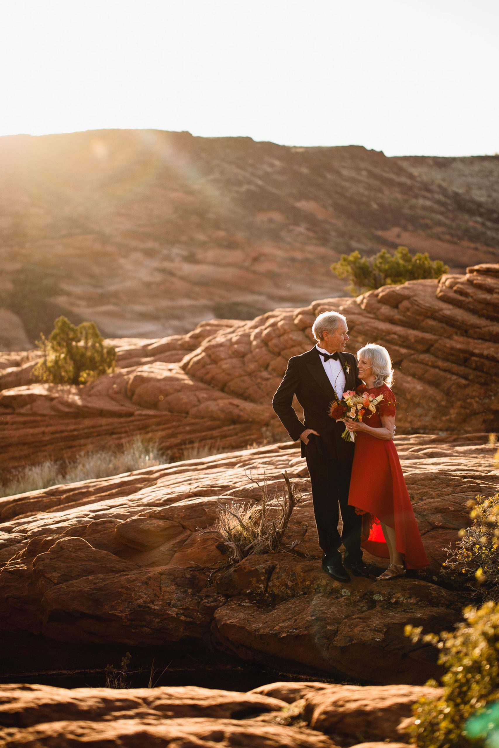 adventure elopement utah desert - recently married couple in the afternoon sun before breathtaking mountain view