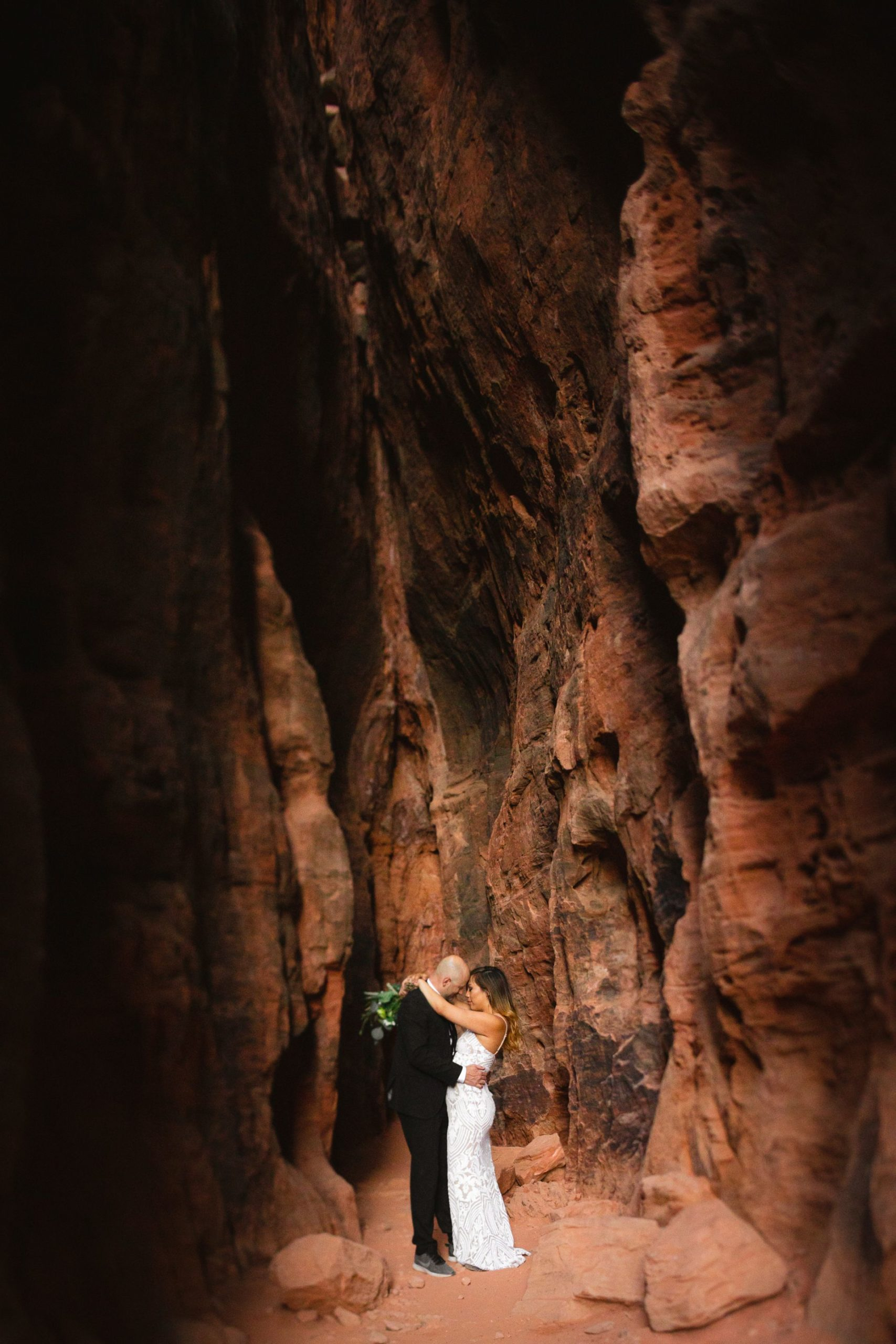 hike out wedding in the utah desert - couple hugging in spectacular canyon